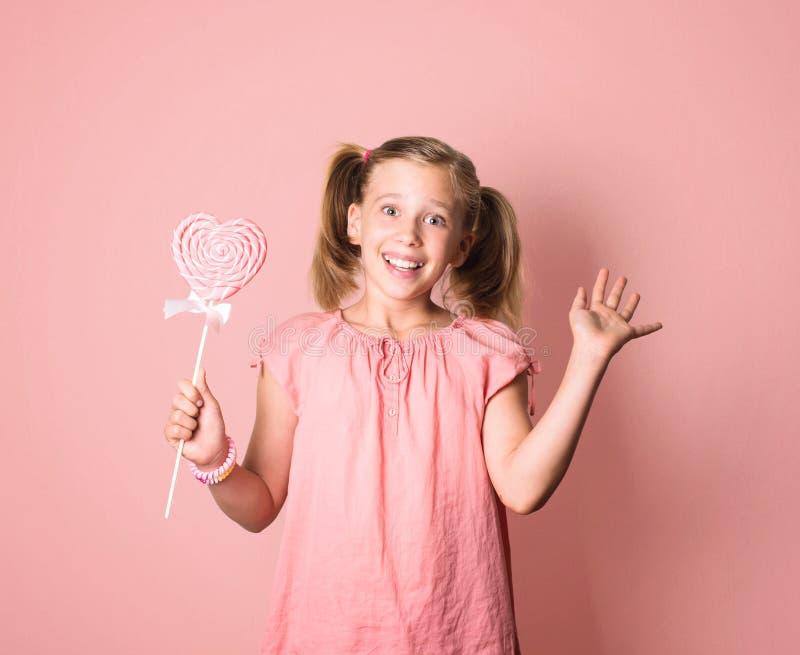 La ragazza sorridente felice in vestito rosa che giudica un grande cuore a forma di ciondola fotografie stock libere da diritti