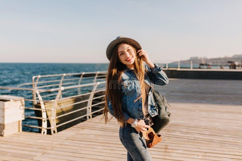 La ragazza sorridente graziosa nel vestito del denim con capelli marroni è venuto al mare ad ascoltare i grida dei gabbiani Lungo fotografia stock