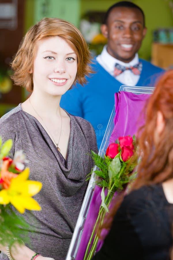 La ragazza sorridente nel negozio di fiore compra le rose immagine stock