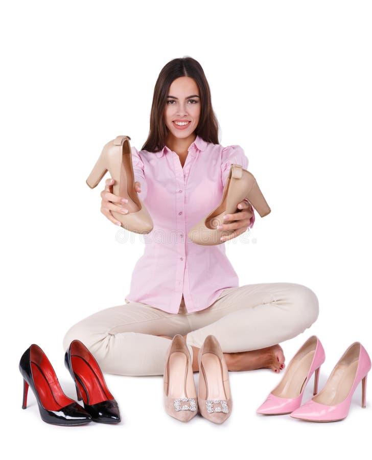 La ragazza sorridente presenta quattro paia delle scarpe a tacco alto isolate su un fondo bianco immagine stock libera da diritti