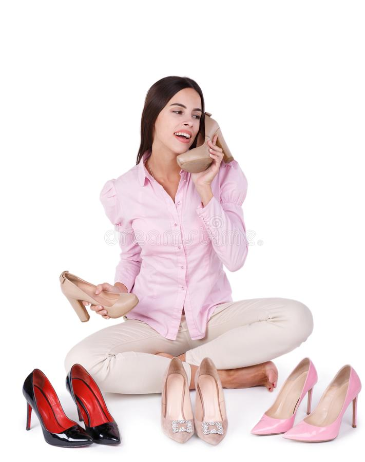 La ragazza sorridente presenta quattro paia delle scarpe a tacco alto isolate su un fondo bianco immagine stock