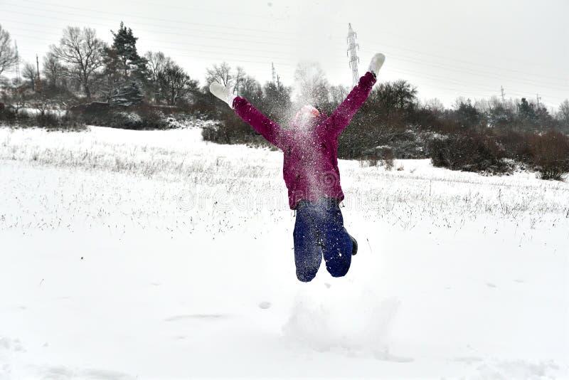 La ragazza sorridente salta e cade nella neve immagini stock libere da diritti
