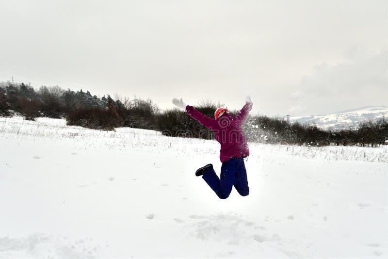 La ragazza sorridente salta e cade nella neve fotografie stock