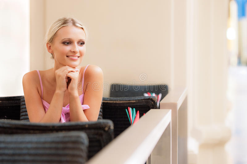 La ragazza sorridente si siede a poca tabella al ristorante immagine stock