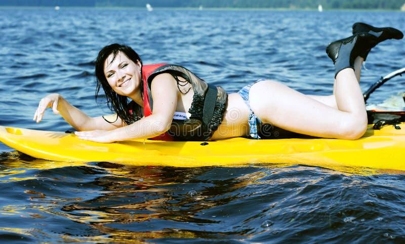 La ragazza sorridente si trova sul praticare il surfing fotografie stock libere da diritti
