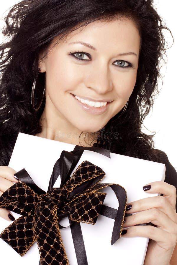 La ragazza sorridente tiene un regalo fotografia stock libera da diritti