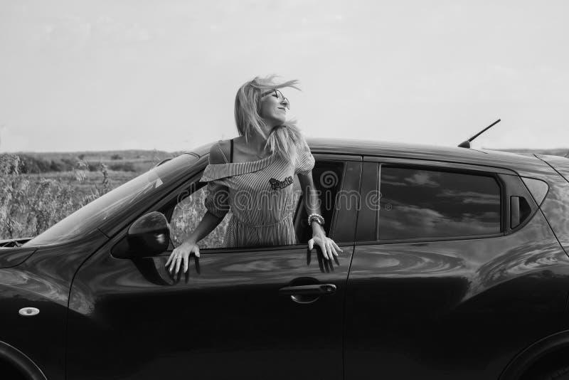 La ragazza sottile è uscito della finestra e dei sorrisi di automobile al sole fotografia stock libera da diritti