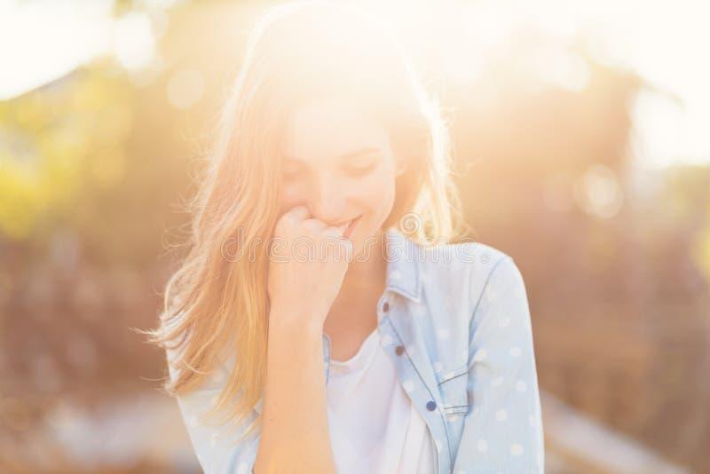 La ragazza splendida con un bello sorriso ed i raggi di sole hanno riflesso sul suo fronte felice immagine stock