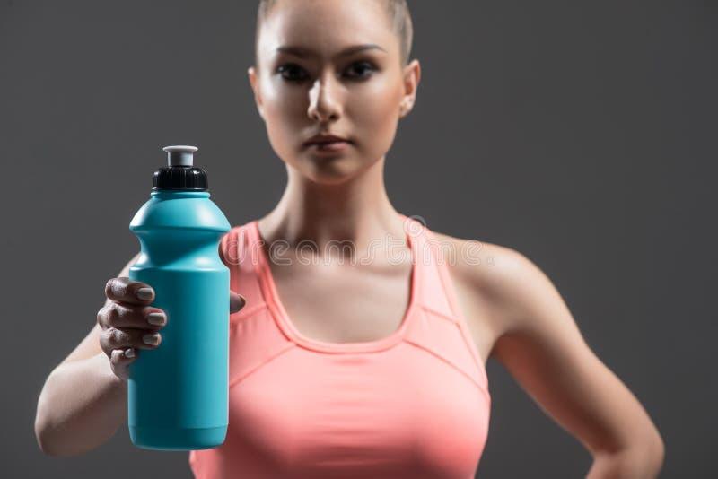 La ragazza sportiva allegra sta mostrando la bevanda sana immagine stock libera da diritti