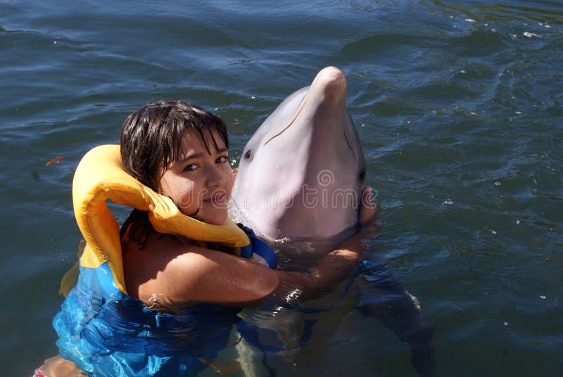 La ragazza sta abbracciando un delfino immagini stock