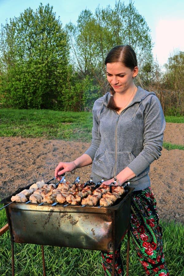 La ragazza sta al barbecue mangal e preparante immagine stock