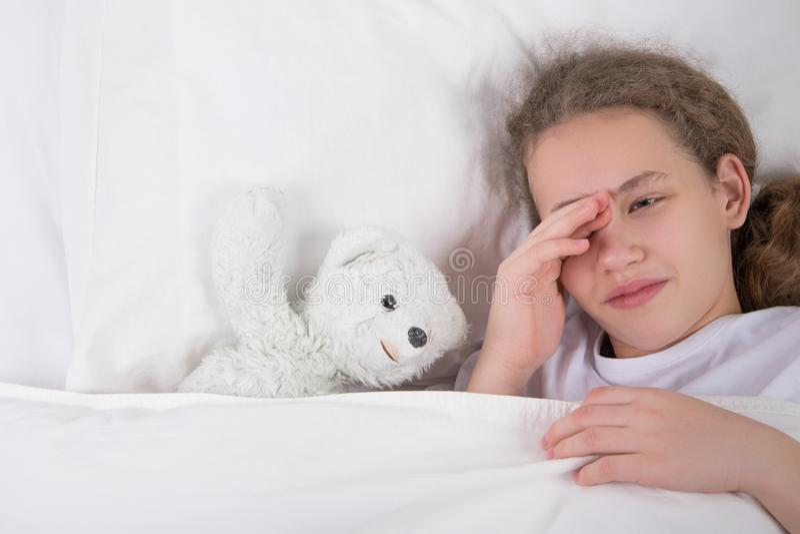 La ragazza sta andando a dormire, si trova a letto accanto ad un orsacchiotto bianco fotografia stock