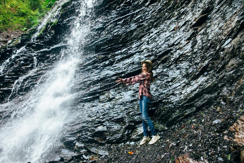 La ragazza sta la cascata vicina e dà le armi a  immagini stock