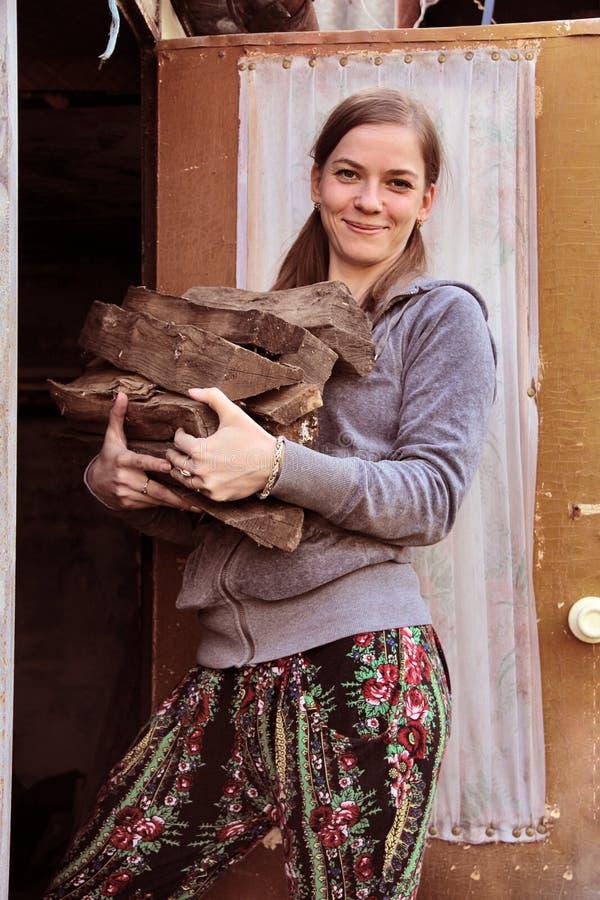 La ragazza sta con legna da ardere in sue mani immagini stock libere da diritti