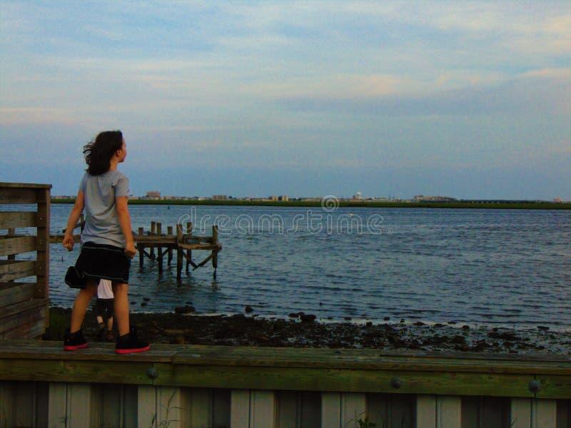 La ragazza sta contro vento sulla riva fotografia stock
