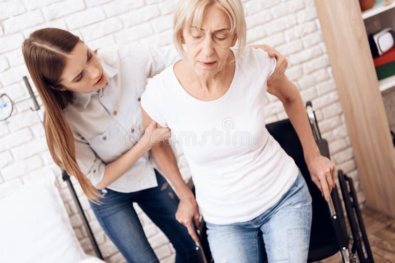La ragazza sta curando la donna anziana a casa La ragazza sta aiutando la donna ad entrare nella sedia a rotelle immagine stock libera da diritti