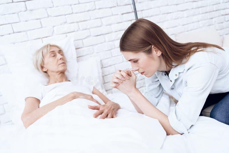 La ragazza sta curando la donna anziana a casa La donna sta ritenendo cattiva, ragazza sta pregando fotografia stock