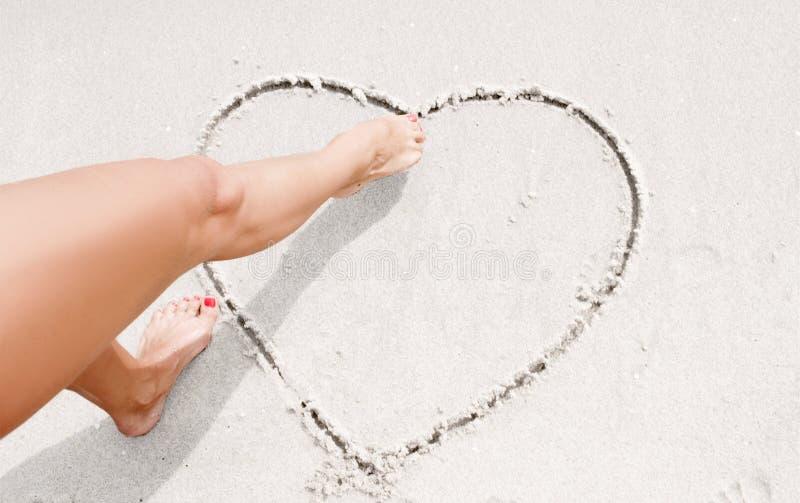 La ragazza sta disegnando il cuore sulla sabbia fotografia stock