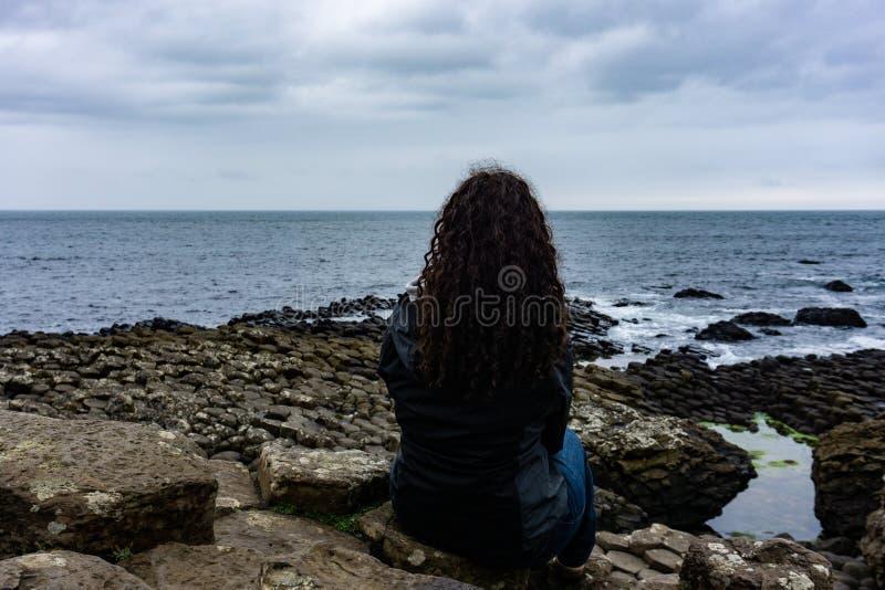 La ragazza sta esaminando l'Oceano Atlantico sulla strada soprelevata del gigante in Irlanda del Nord fotografia stock