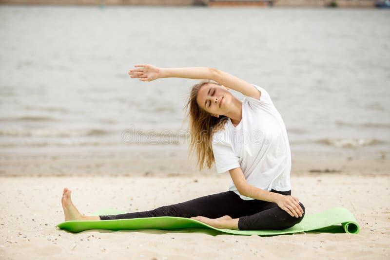 La ragazza sta facendo l'allungamento sulla stuoia di yoga sulla spiaggia sabbiosa un giorno caldo fotografia stock libera da diritti