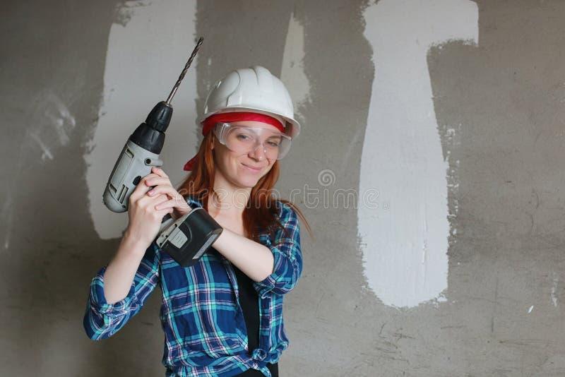 La ragazza sta facendo le riparazioni nell'appartamento Muoversi domestico verso un nuovo appartamento Il lavoratore fa le ripara fotografie stock