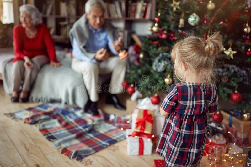 La ragazza sta giocando davanti ad un albero di Natale decorato immagini stock libere da diritti