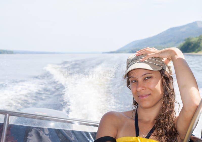 La ragazza sta guidando sul motoscafo sul fiume nel pomeriggio dell'estate immagine stock libera da diritti