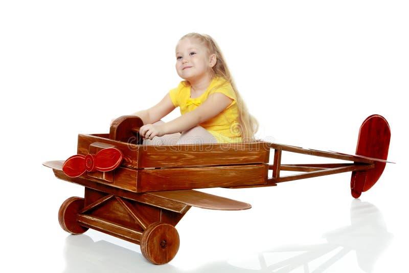 La ragazza sta guidando un aereo del giocattolo immagine stock libera da diritti