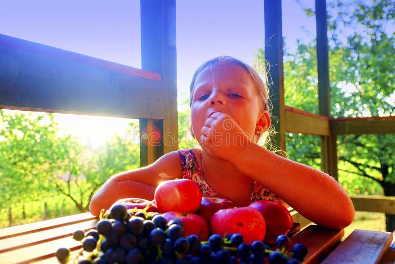 La ragazza sta mangiando la frutta Mele ed uva su una tavola La bambina sta sedendosi ad una tavola su una veranda e su un eati immagini stock