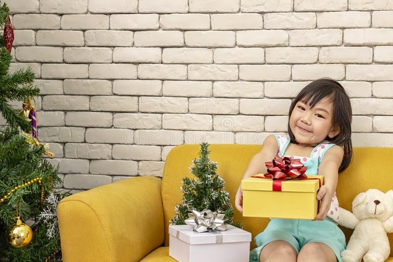 La ragazza sta presentando un regalo di Natale ragazza che mostra il contenitore di regalo Bambino asiatico sveglio che tiene una fotografie stock