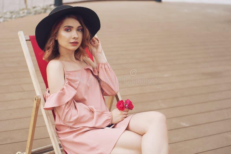 La ragazza sta riposando su una chaise-lounge La ragazza in un bello vestito rosa, cappello alla moda nero sta riposando su un vi fotografia stock libera da diritti