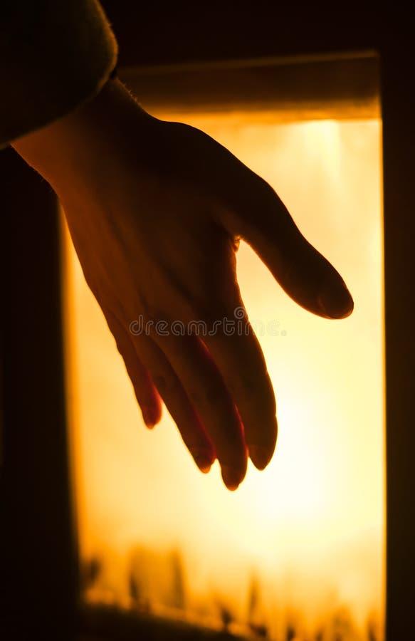 La ragazza sta riscaldando per sentire la mano dalla fornace immagine stock