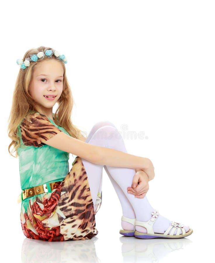 La ragazza sta sedendosi lateralmente sul pavimento che abbraccia le sue ginocchia fotografia stock
