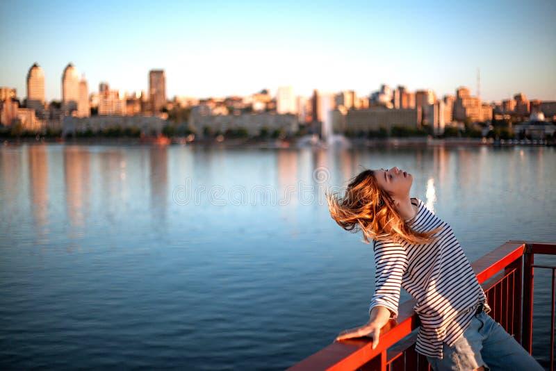 La ragazza sta sedendosi sull'inferriata del ponte fotografie stock libere da diritti