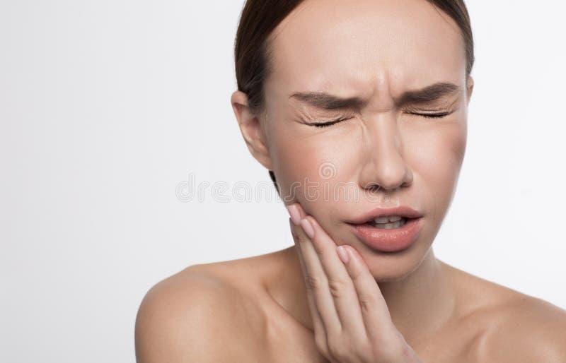 La ragazza sta soffrendo dal dolore dentario fotografia stock libera da diritti