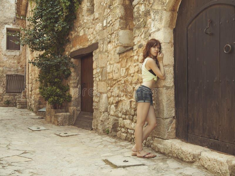 La ragazza sta stando sulla via di vecchia città immagine stock