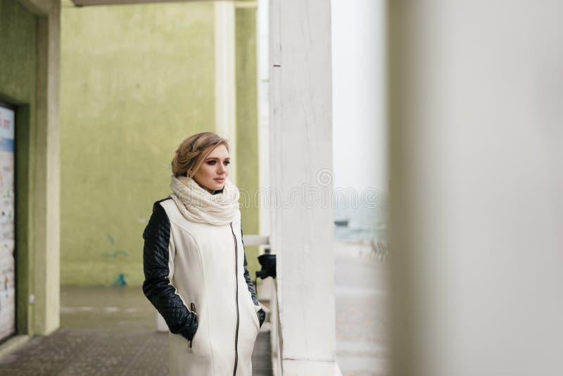 La ragazza sta stando vicino alla colonna ed a fissare immagini stock libere da diritti
