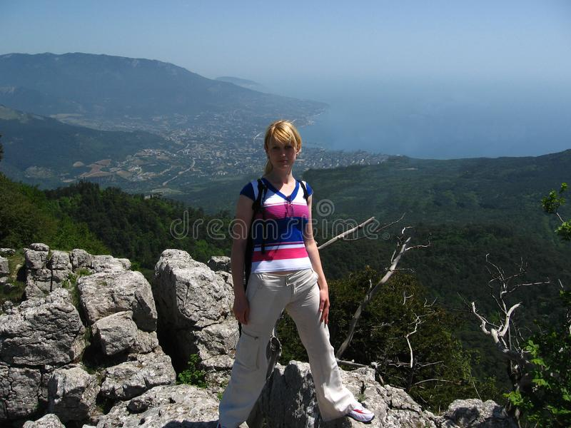 La ragazza sta sulle rocce contro i precedenti fotografia stock libera da diritti