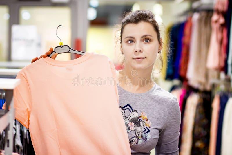 La ragazza sta tenendo la blusa nel boutique di modo la donna compra i vestiti in deposito La ragazza è sull'acquisto immagine stock
