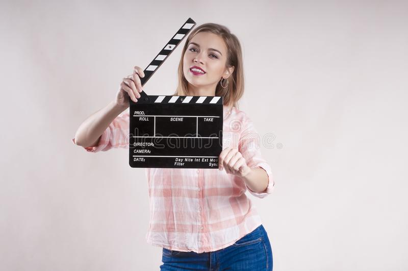 La ragazza sta tenendo un ciac e una posa inizio del produttore su fondo bianco fotografie stock libere da diritti