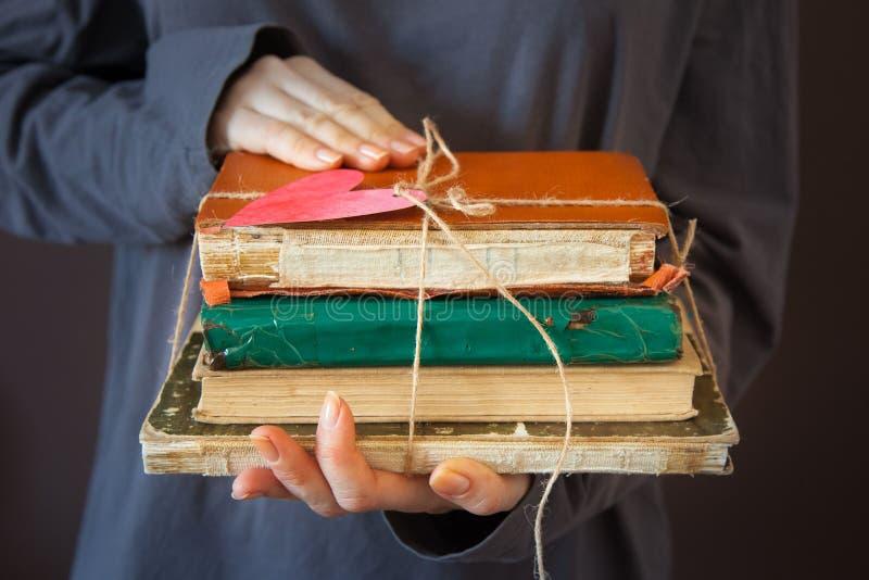 La ragazza sta tenendo una pila di vecchi libri in sue mani Wi legati fotografia stock libera da diritti