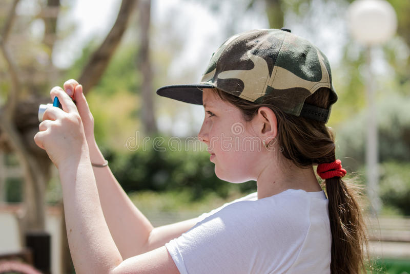 La ragazza sta un giorno soleggiato ed impara prendere le immagini con una macchina fotografica fotografie stock libere da diritti