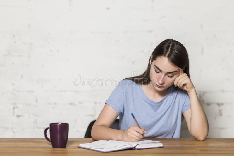 La ragazza stanca scrive in un taccuino Si siede ad una tavola nella stanza Sulla tavola è una tazza di caffè fotografia stock