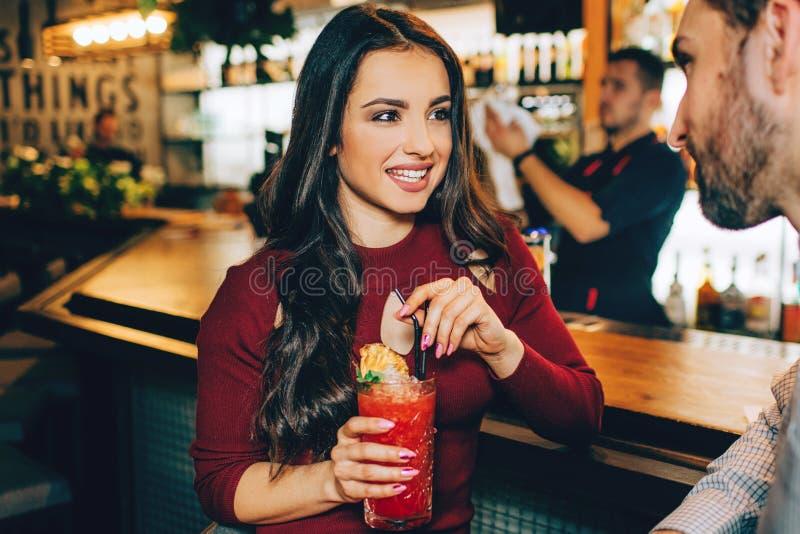 La ragazza stupefacente sta sedendosi al supporto del ` s del barista e sta tenendo un vetro del cocktail in sue mani Sta sorride immagini stock