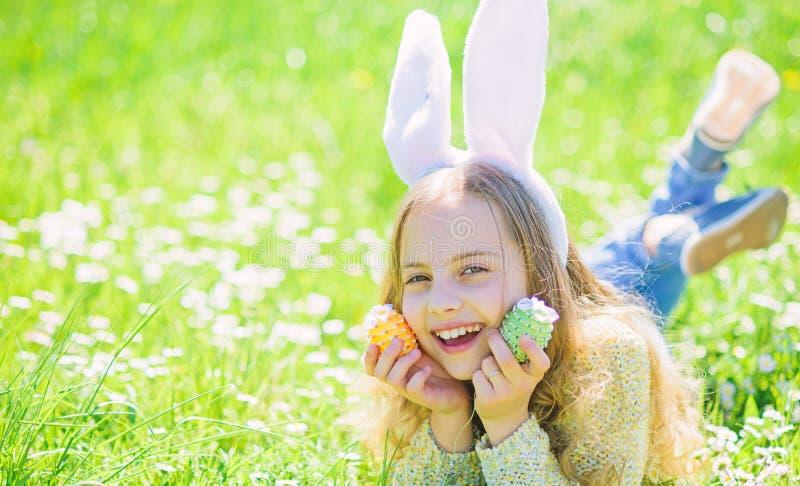 La ragazza sul fronte felice tiene le uova di Pasqua in mani, erba su fondo Bambino con le orecchie del coniglietto che si trovan fotografia stock libera da diritti