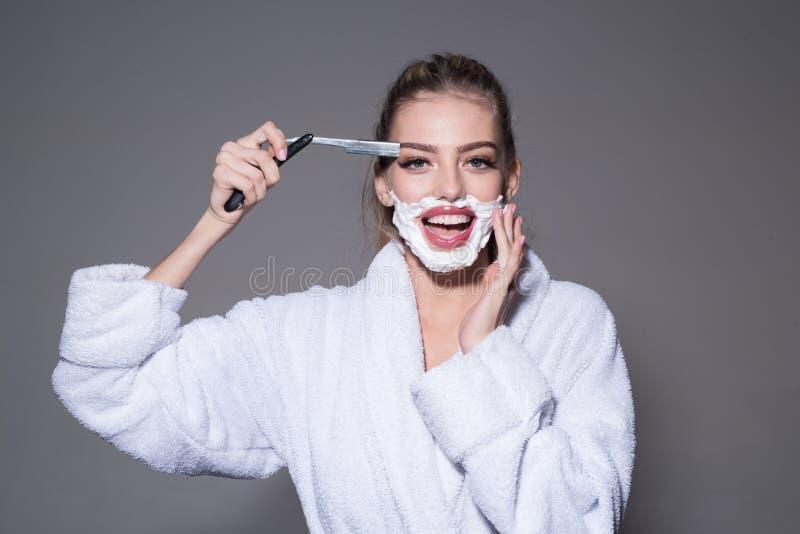 La ragazza sul fronte sorridente porta l'accappatoio, fondo grigio Gioco di signora con la lama tagliente del rasoio diritto Barb immagine stock