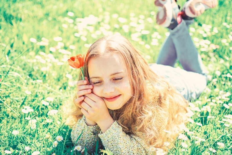 La ragazza sul fronte vago tiene il fiore rosso del tulipano, gode dell'aroma Concetto della rottura di primavera Il bambino gode fotografia stock libera da diritti
