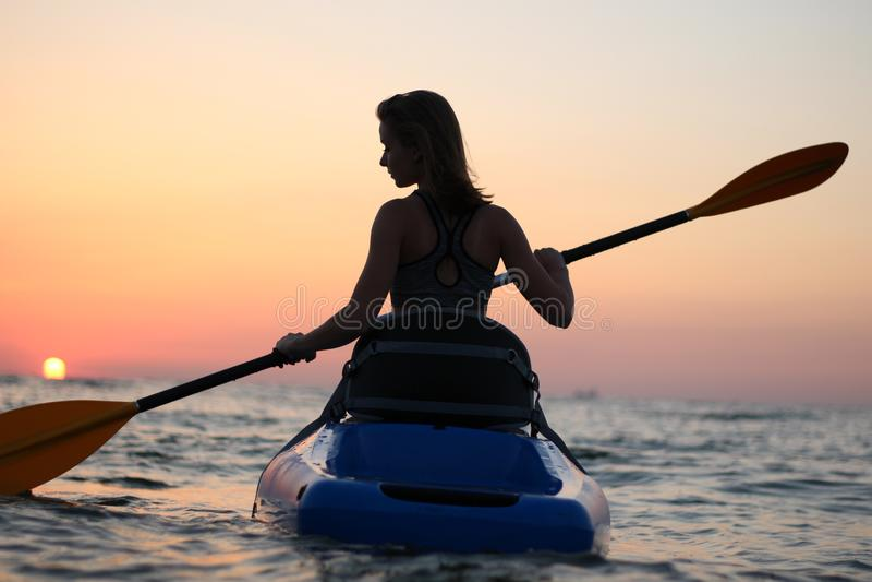La ragazza sul kajak accoglie l'alba del sole immagini stock libere da diritti