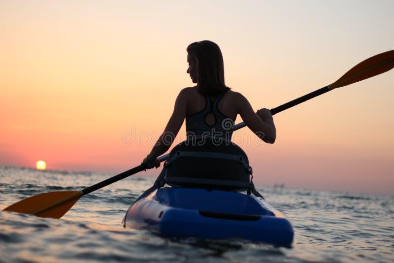 La ragazza sul kajak accoglie l'alba del sole fotografie stock