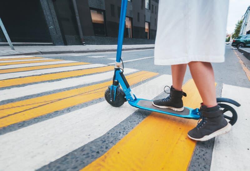 La ragazza sul motorino elettrico di scossa ad un passaggio pedonale, primo piano delle gambe fotografie stock libere da diritti